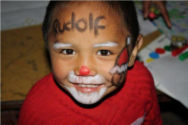 Child in a care center with festive face paint on a Projects Abroad volunteer placement