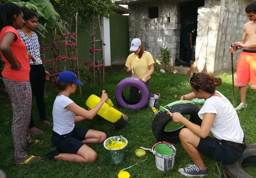 Volunteers paint a day care center's garden colorful during their Care Project in Sri Lanka