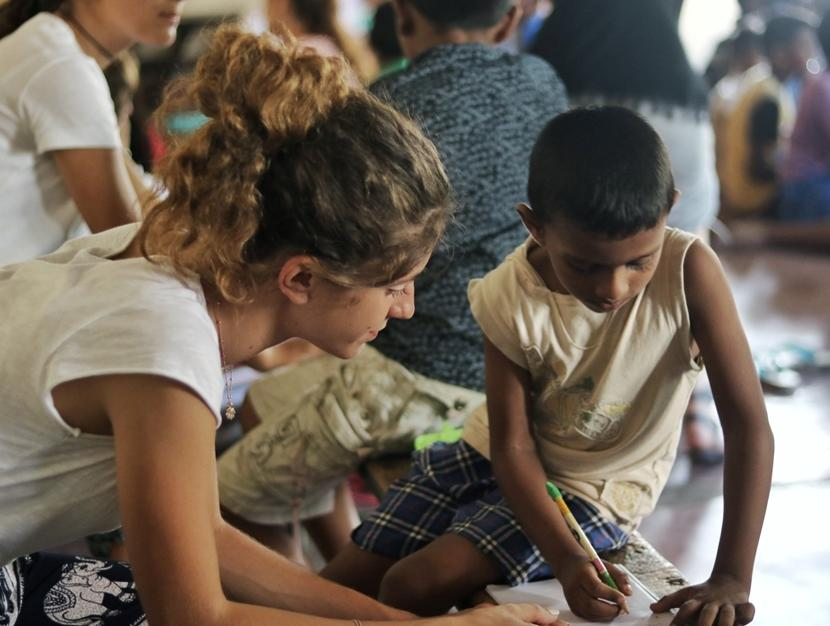 A Projects Abroad High School volunteer helps a young Sri Lankan boy improve his writing.