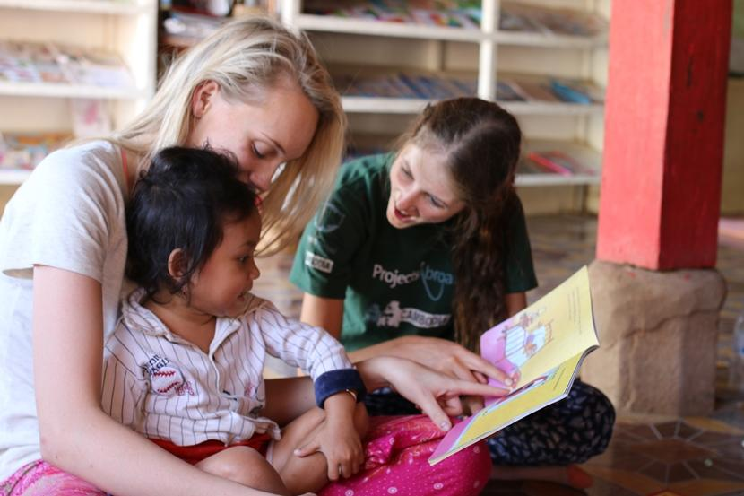 Projects Abroad Care and Community volunteer reads to the children at her placement in Cambodia