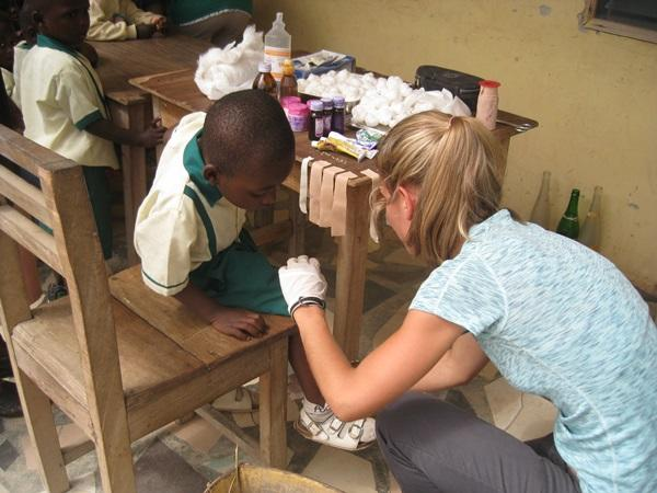 Public Health Intern dressing a child's wound in a village in Ghana