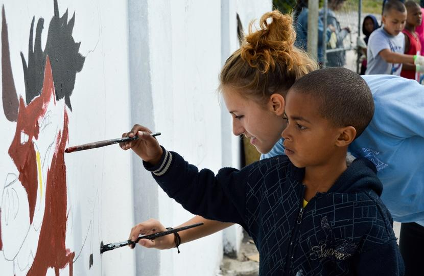 Round Square student and local South African boy paint a wall mural