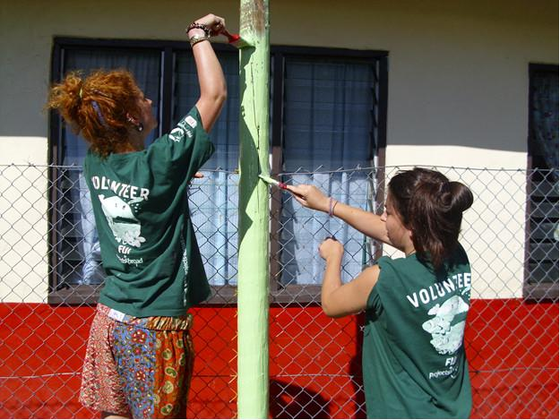 Volunteers painting together on a project with Projects Abroad