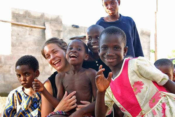 A volunteer laughing with a group of children at a Childcare placement in Ghana
