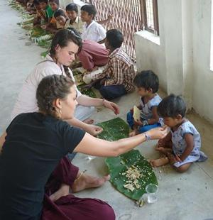Projects Abroad volunteers help feed children at a care center in India