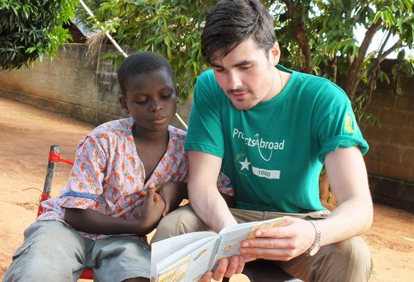 British Projects Abroad volunteer helps a boy in the Reading Club with his book in a care placement in Togo