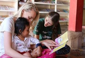 Two 19+ Care & Community volunteers read stories to children at their Cambodian placement.
