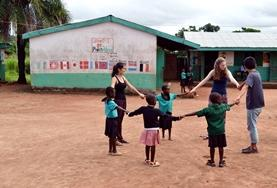 19+ Care & Community volunteers play a game with children outside the classroom in Ghana.
