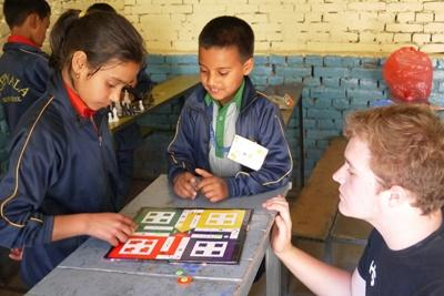 Projects Abroad Care & Community volunteers helps Nepalese kids play a game.