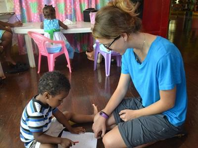 Projects Abroad volunteer helps a child with an educational activity at a care center.