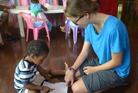 A child completes an activity with the help of a volunteer in Belize.