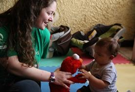 A volunteer plays with a young child at a care center in Costa Rica.