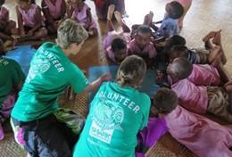 A group of volunteers help children with an educational activity in Fiji.