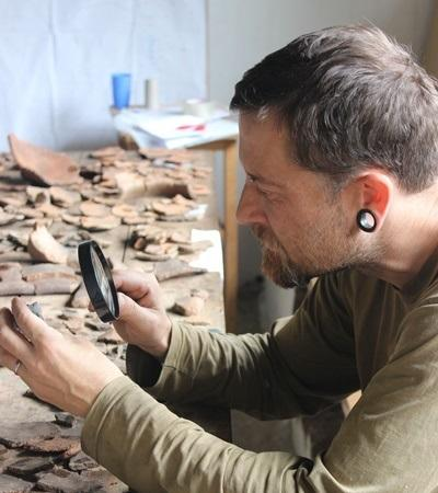 A Projects Abroad Archaeology volunteer on the Inca Project uses a magnifying glass to take a close look at ceramics found in Huyro, Lucumayo Valley.