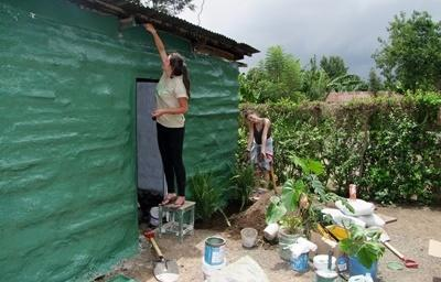 Volunteer paint a community building on the Building project in Tanzania