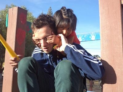 A Bolivian child enjoys playing with a male Care volunteer