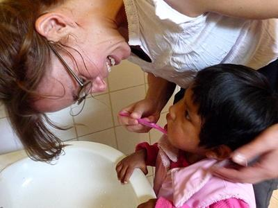 Volunteer helping a young girl to brush her teeth at a care center in Bolivia