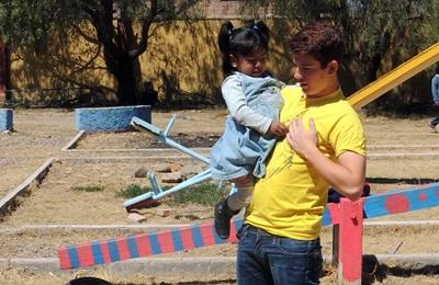 A Bolivian child is picked up by a Care volunteer in Bolivia