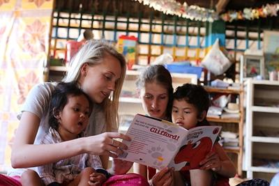 Students who chose to volunteer abroad with Projects Abroad in Cambodia read with the children at a day care center