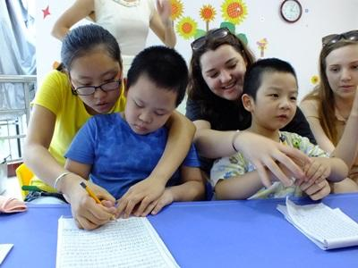 Chinese children finish an educational activity with the help of Care volunteers