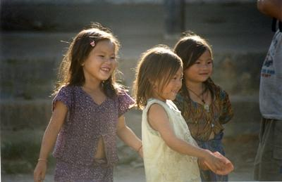 A group of local girls play together in the Laos sunshine.