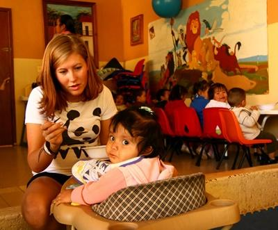 Volunteer feeding a young girl at a care cener in Mexico
