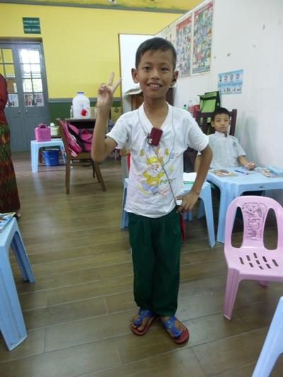 A child from Myanmar poses for the camera at a local Care facility