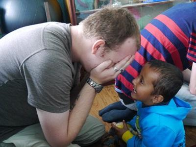A child enjoys a game with a Care volunteer in Nepal, Asia