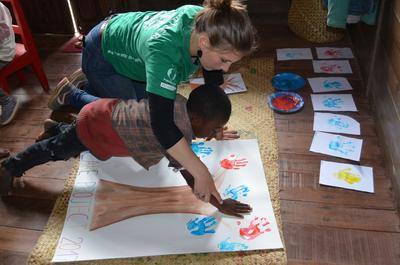 Volunteer helps a child paint a tree in a Madagascar care center