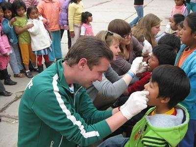 Care Project volunteer performing dental checkups on kids in childcare centers in Peru