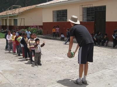 A group of Peruvian children enjoy an outdoor activity with a volunteer