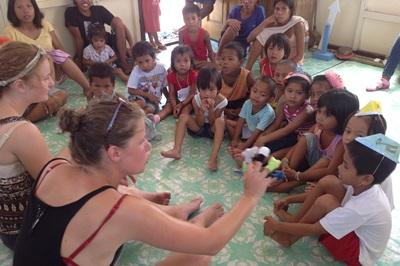 Volunteers and children sit in morning meeting at the beginning of a day on the Care project in the Philippines