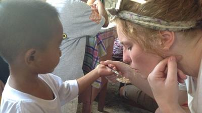 Volunteer helps with meal time in a care center for children in the Philippines