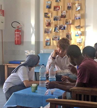 Projects Abroad Refugee Project volunteer has a discussion with refugees and migrants in Italy, Europe
