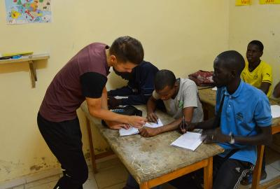 Projects Abroad volunteer helps a group of street children with a homework exercise in Senegal, Africa.