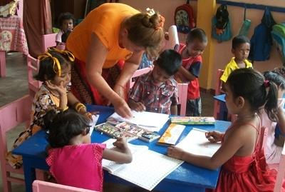 Sri Lankan children complete an activity with the help of a Projects Abroad volunteer