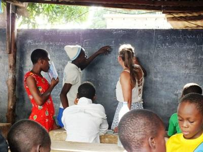 A Projects Abroad volunteer assists Togolese teenagers with homework at her care center placement