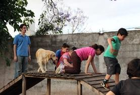 Children interact with a trained dog at the Canine Therapy Project in Argentina.