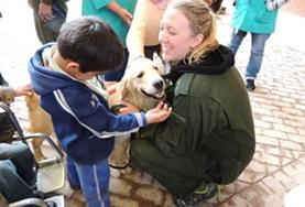 A volunteer helps a child interact with a dog at the Canine Therapy Project in Bolivia.
