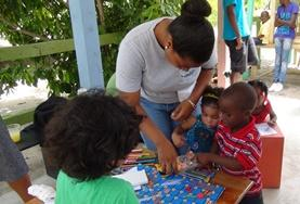 A volunteer helps children with an activity in Belize.