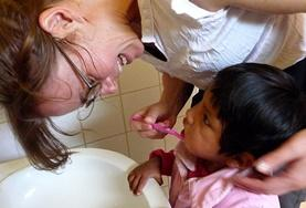 A volunteer helps a child brush their teeth in Bolivia.