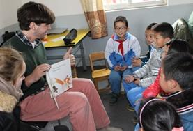 A volunteer reads aloud to children in China.