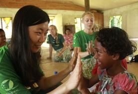 A volunteer plays a game with a child in Fiji.