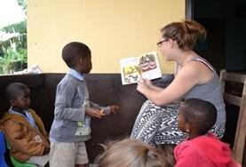 A volunteer reads a story to children in Ghana.