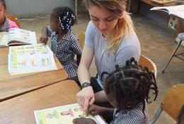 A volunteer working with children in Jamaica helps with a reading activity.