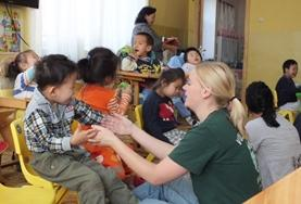 A child plays with a volunteer at a care center in Mongolia.