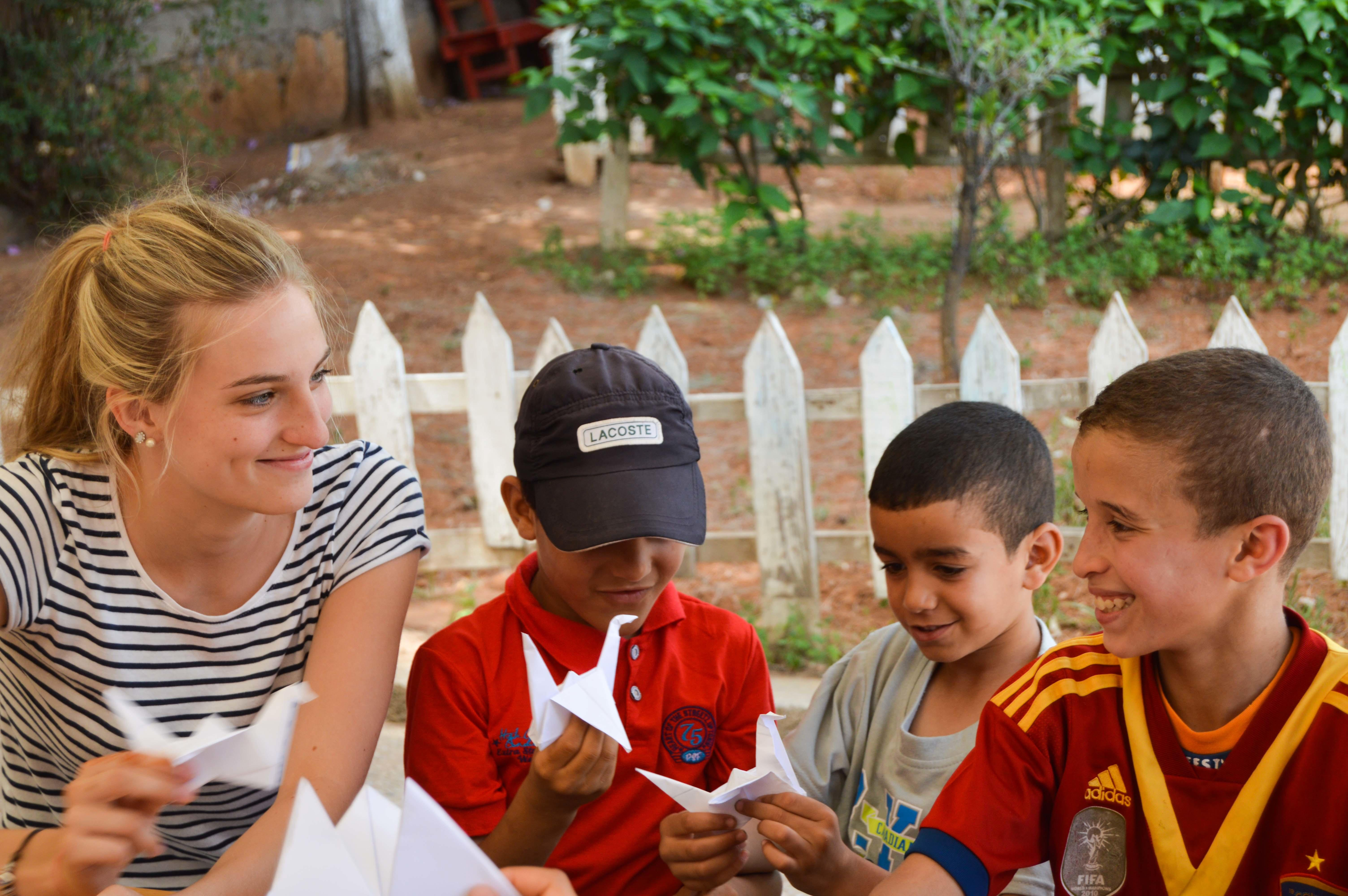 A volunteer helps children with an arts and crafts activity in Morocco.