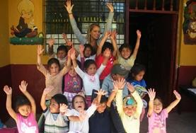 A volunteer with children at a day care center in Peru.