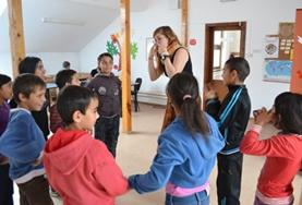 Children participate in an activity with a volunteer in Romania.