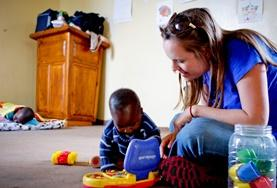 A volunteer helps a child develop their motor skills in South Africa.